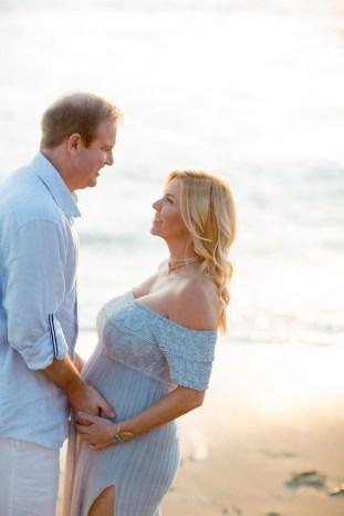 orange county maternity photographer nicole caldwell crystal cove beach couple holding hands