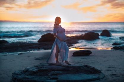 orange county maternity photographer nicole caldwell crystal cove beach pregnant mom on rocks in flowy dress