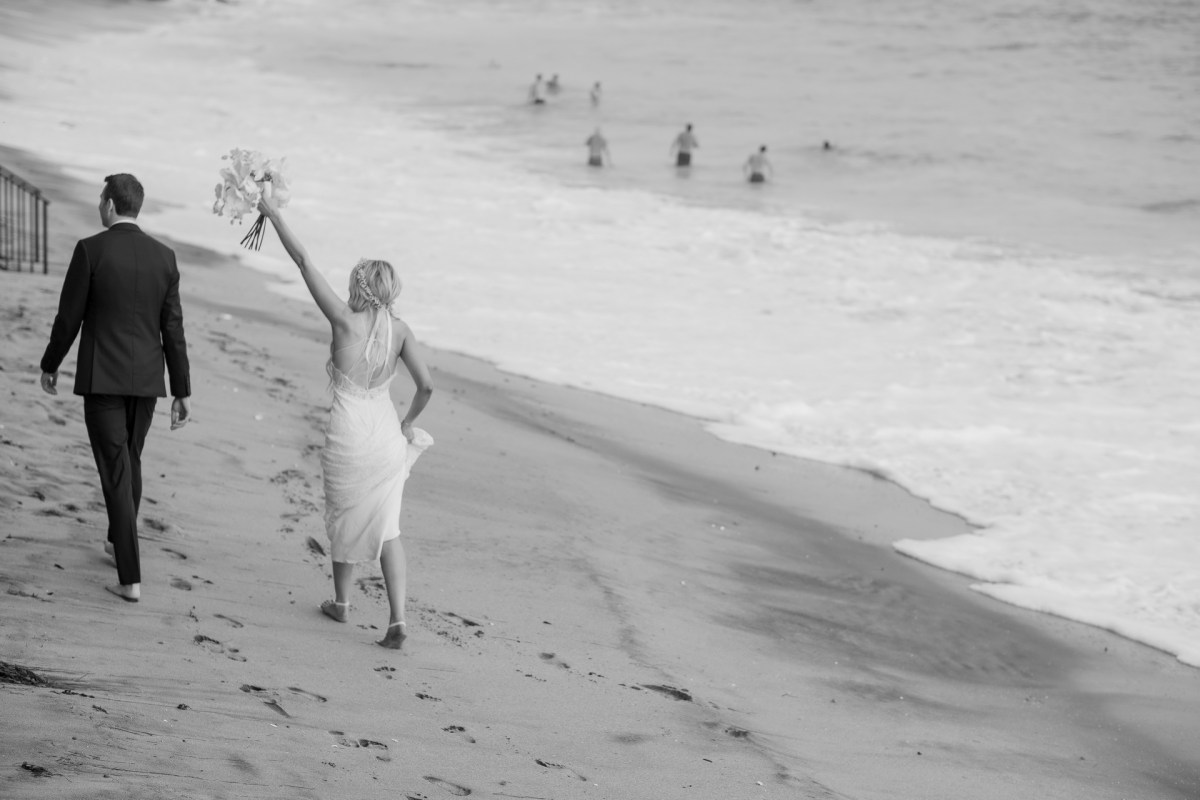bride holding bouquet in air on beach wedding photos surf and sand resort laguna beach