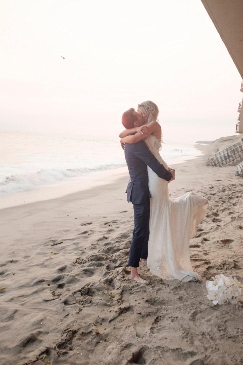 groom lifitng bride in sand wedding photos surf and sand resort laguna beach