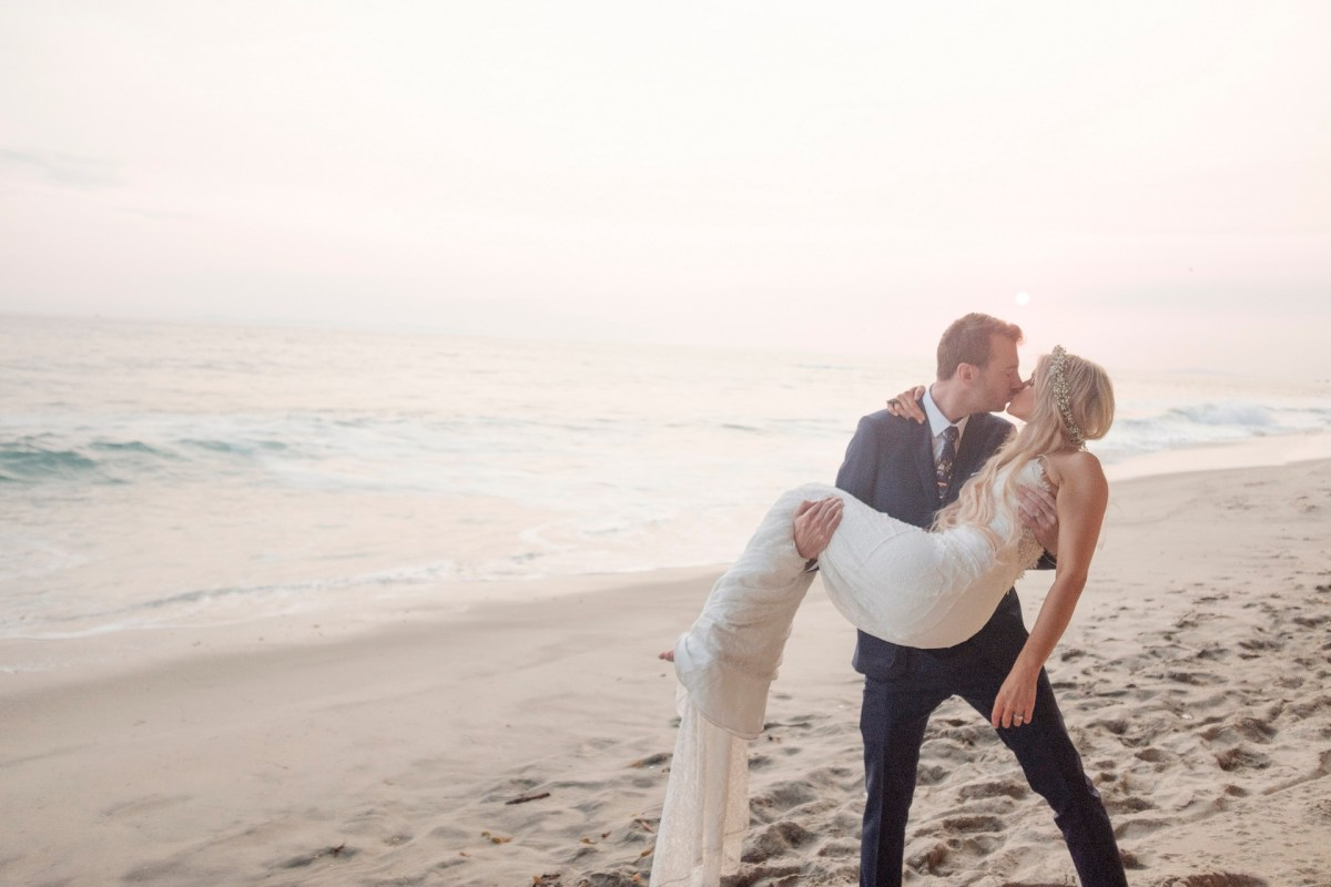 groom holding bride kissing on beach wedding photos surf and sand resort laguna beach