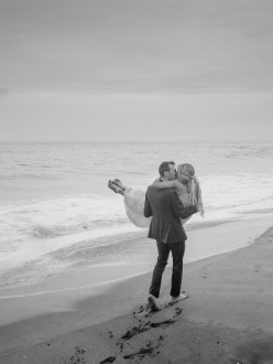 groom carrying bride through the sand on laguna beach wedding photos surf and sand resort laguna beach