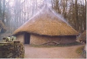"Recreated Celtic Village, Museum of Welsh Life. The open fire within the circular hut gives the thatched roof a ""steaming"" effect. Three round wattle-and-daub huts are surrounded by a ditch and wooden palisade. (Source: Wikimedia Commons)"