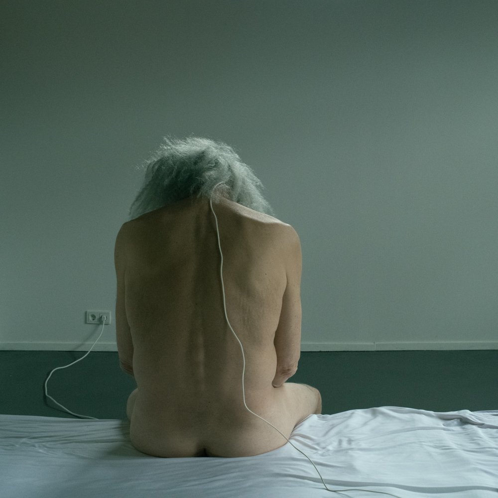 Photo in color man with long gray hair sitting on a bed. Electric wire connects him with wall outlet