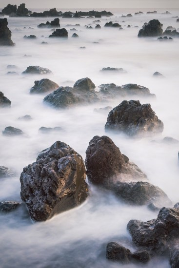 A 15-second exposure created a cloud-like effect to the water in this rocky shoreline.