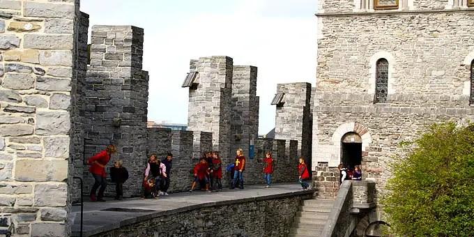 Gruppe von Kindern in Ritterkostümen auf einer Mauer der Wasserburg Gravensteen - Flandern Rundfahrt