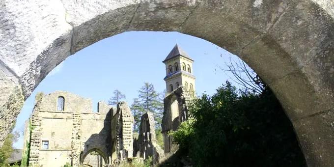 Blick durch einen Steinbogen auf Ruinen der Trappistenabtei in Orval im Belgien Urlaub