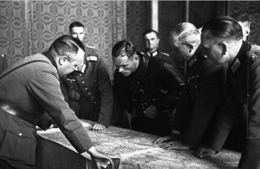 """Nasz drug Gitler… Gen. Heinz Guderian (na pierwszym planie z lewej) prowadzi naradę oficerów sojuszniczych armii – Wehrmachtu i Armii Czerwonej. Ustalają szczegóły linii demarkacyjne"""" między agresorami na terytorium zniewolonej Polski. Źródło: Wikipedia, domena publiczna."""