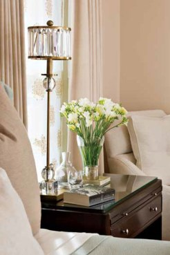 A crystal-and-brass Currey & Company lamp sits on a Barbara Barry bedside table for Baker on her side of the master bedroom, above; the bedside table on his side is from Baker's Milling Road series. A comfy Kravet chair rests in one corner.