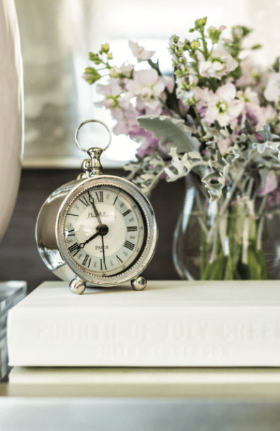 Bringing a note of old- school charm to the master bedroom is a classic alarm clock perched on a bedside table. Fresh flowers pick up the palette of muted hues.