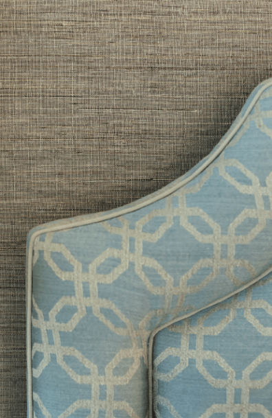 The custom headboard is upholstered in Holland & Sherry fabric. Its pale-blue trellis-like pattern stands out against a subtly striated handwoven natural grass-cloth wallcovering by Hartmann & Forbes.