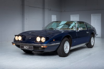 Front quarter view of a blue 1971 Maserati Indy America 4700 with pop-up headlights