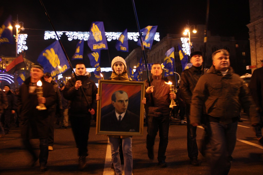 People holding UPA (horizontal red and black) and Svoboda (3 yellow fingers on blue) flags march through Kyiv to the honor of the Nazi ally, Bandera.