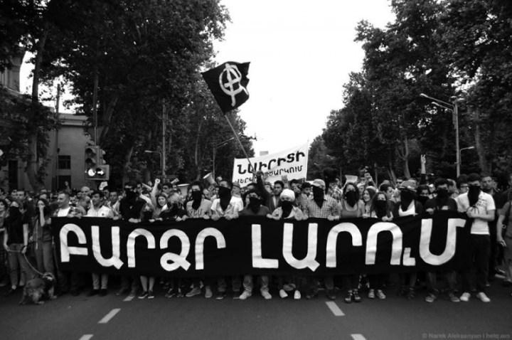 """Надпись на черной растяжке: """"Высокое напряжение"""" Надпись на белом баннере: """"Перезапуск Наирита""""  Создающееся впечатление, что на фотографии запечатлен анархический блок, обманчиво. Анархистов на шествии было всего несколько человек."""