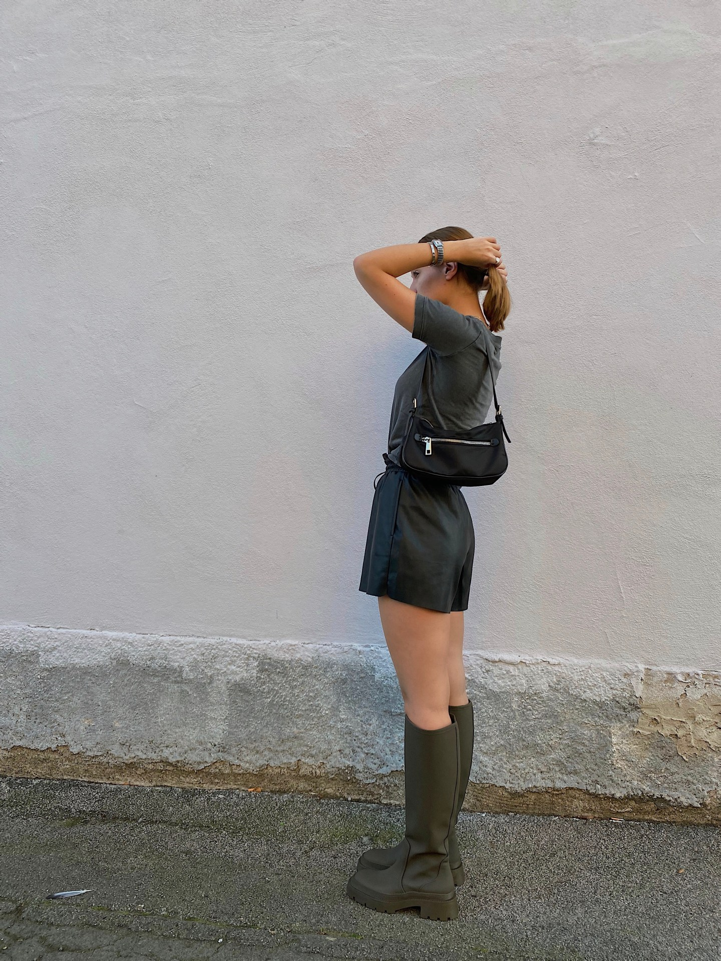 Jung Girl wearing knee-high wellington boots in khaki, short black fake leather shorts and a grey tshirt.