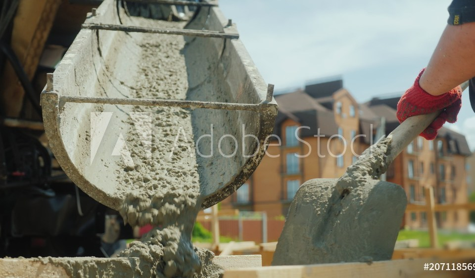 Building a cottage. Workers take concrete from a mixer into a wooden formwork