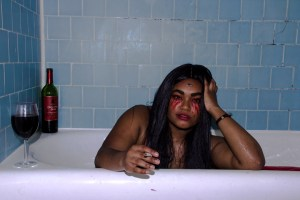 girl smoking cigarette in bath tub with wine