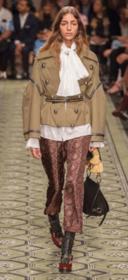 BURBERRY The embellished military jacket is a signature Burberry look with printed pants and a thick-strapped bag. The bell sleeve blouse creates a heavier look elaborating on the details of the military jacket.