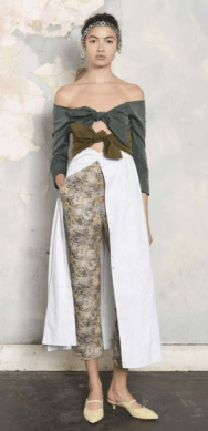 ISA ARFEN The double tone top of green shades gives an earthy tone, especially with the floral printed cropped pants and neutral sandals. The headband sets a bohemian vibe to the up-and-in-a-bun hairstyle. The white textured wrap creates the warmth necessary to a Fall collection.
