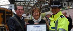 Campaign Director Dave Scott and Roseanna Cunningham MSP present Area Commander Ellie Bird with a certificate in recognition of British Transport Police's commitment to tackling sectarianism.