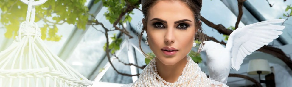Bridal makeup artist. Dubai bride with beautiful bridal makeup and a white dove on shoulder