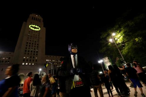 A person wearing a Batman costume poses for photos as a bat-signal is projected on City Hall in honor of late actor Adam West in Los Angeles