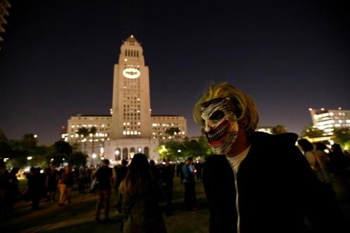A person wears a Joker mask as the bat-signal is projected on City Hall in honor of late actor Adam West in Los Angeles