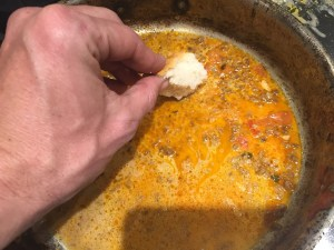 Sopping up broth in a pan on the stove