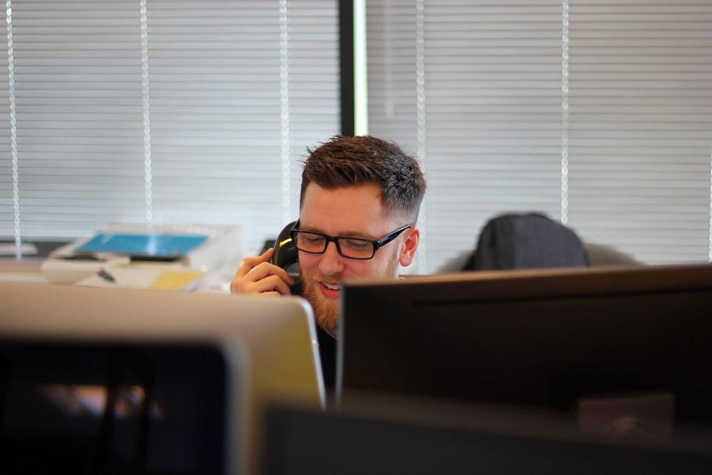 Man talking on phone at computer