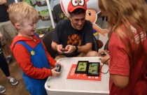 IMAGE DISTRIBUTED FOR NINTENDO OF AMERICA - Parker G., 7, Bill V. and Ava T., 8, left to right, of Rotterdam, NY, gather at the Nintendo NY store in Rockefeller Plaza on Sunday, Oct. 7, 2018, in New York, to celebrate the launch of the Super Mario Party by playing the new Toad's Rec Room mode using two Nintendo Switch systems. An action-packed party game with 80 interactive mini-games, Super Mario Party is now available for the Nintendo Switch system. (Diane Bondareff/AP Images for Nintendo of America)
