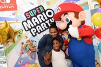 IMAGE DISTRIBUTED FOR NINTENDO OF AMERICA - Shirley M. and Gabriella A., 5, of New York, NY, celebrate the launch of the Super Mario Party and Luigi's Mansion games by posing with Mario during a special event at the Nintendo NY store in Rockefeller Plaza on Sunday, Oct. 7, 2018, in New York. An action-packed party game with 80 interactive mini-games, Super Mario Party is now available for the Nintendo Switch system. (Diane Bondareff/AP Images for Nintendo of America)