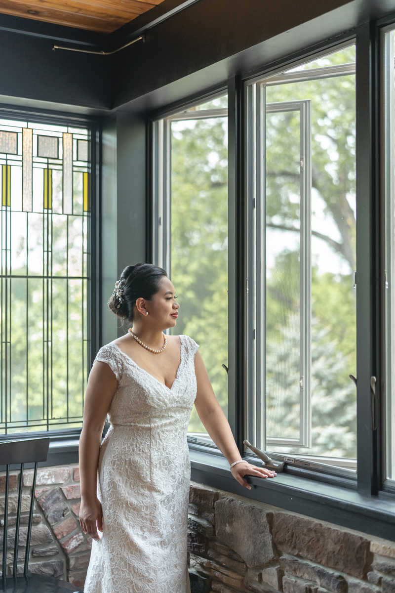 Beatrice stands at a window on the second floor of the Mohawk house for a beautiful bridal portrait.