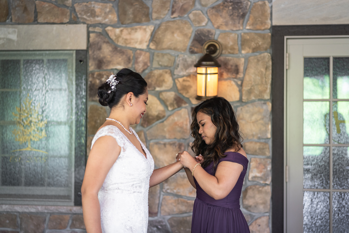 Beatrice is getting ready for her wedding with her friend helping her put on a bracelet inside one of the rooms at Mohawk House Sparta, NJ.