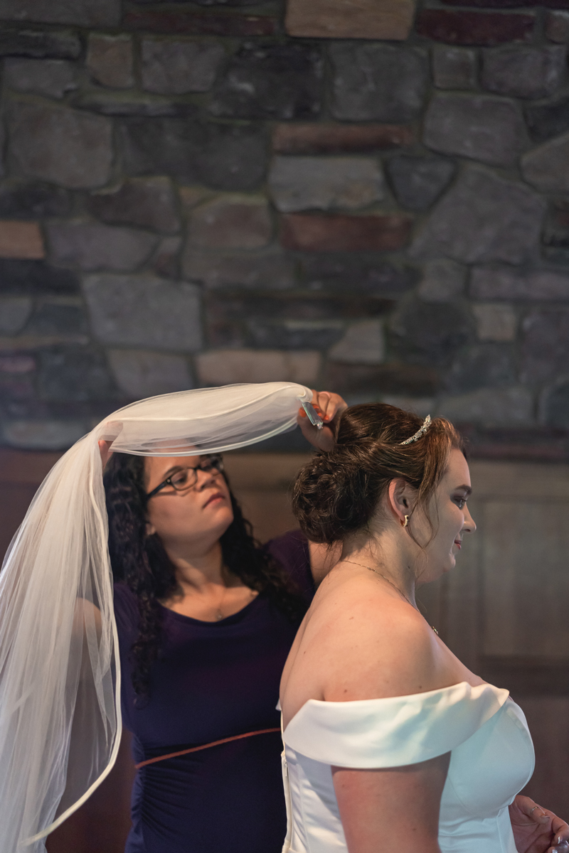 Jennifer is getting ready for her wedding in one of the rooms of the Mohawk House with her friend helping her put on a wedding veil.