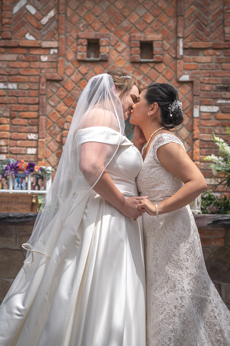 Jennifer and Bea sharing a kiss on a sunny day at their Mohawk House wedding.