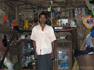 উ সাই খয় - দাঁত কেলিয়ে হাসি; পিছনেই দেখা যাচ্ছে তাঁর পূজার সরঞ্জামাদি (ছবি: লেখক)