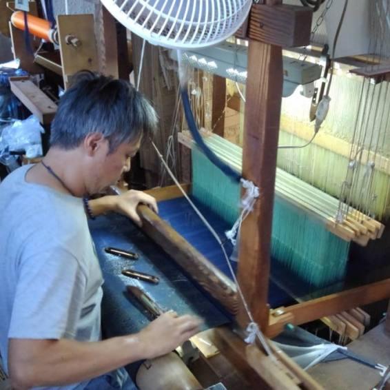 手織り作業、杼を通す