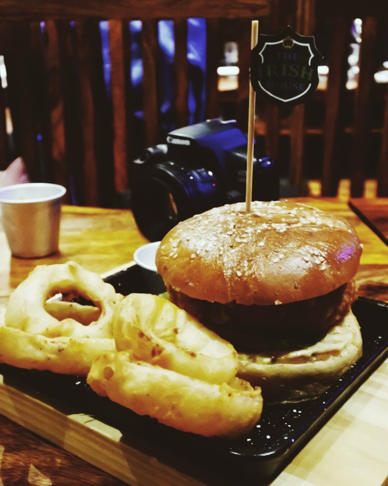 The burger accompanied by onion rings