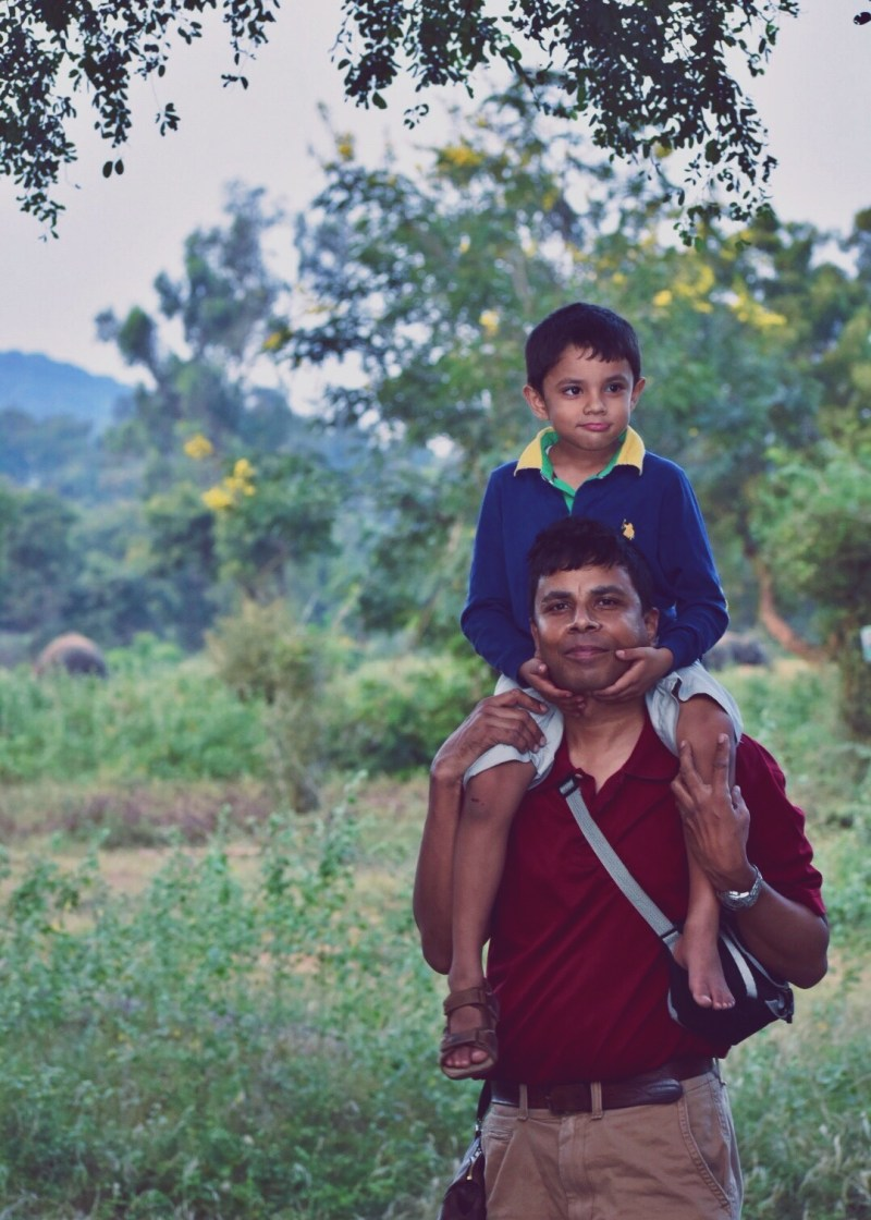Father, son, and elephant in the background