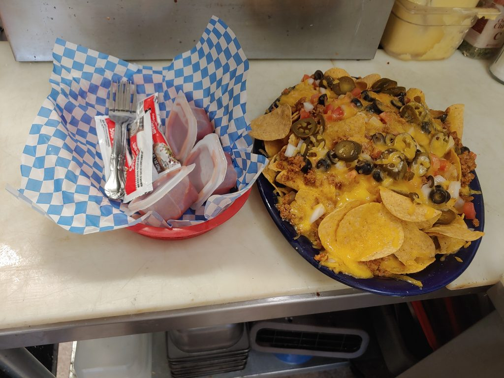 plate of nisqually nachos served with seasoned ground beef, tillamook cheddar cheese, black olives, fresh tomatoes with a basket of sour cream and salsa packages