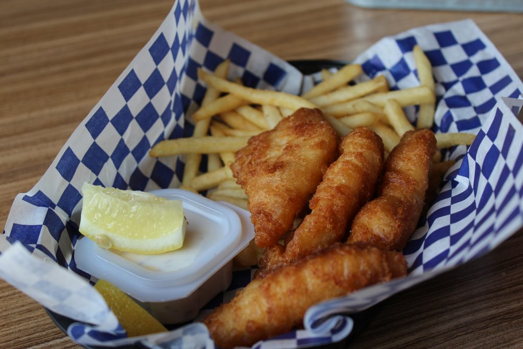 basket of fish and chips served with a side of fries and tartar sauce topped with a lemon wedge for zest