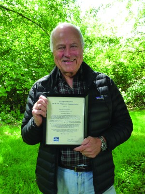 Mike Ryherd holds the certificate verifying that he and his wife, Anne, were the winning bidders for 25 carbon credits at the Land Trust's annual auction. The Ryherds' credits are the first ever to be retired to offset the carbon emissions of private individuals in South Puget Sound. They are the equivalent of approximately one-half of an average local household's annual carbon emissions.