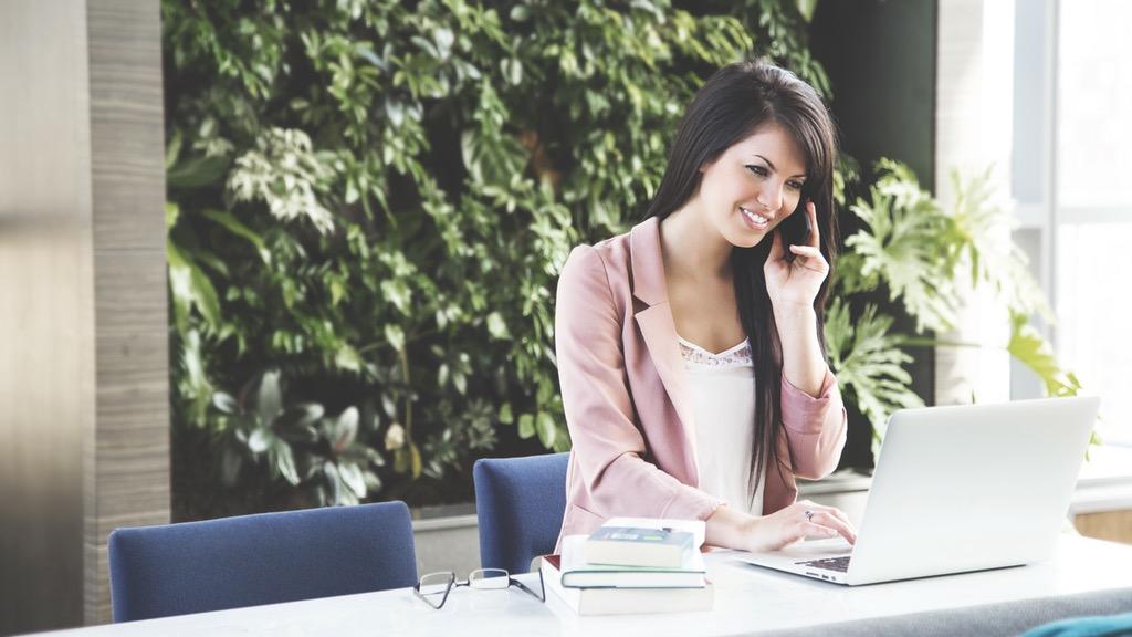 mujer hablando por teléfono y mirando la pantalla de una computadora, el embudo de conversión representa las distintas etapas del comprador