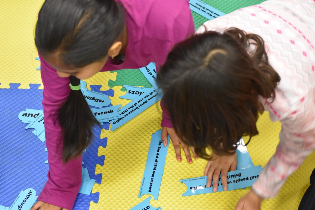 Students at HEROES build sentences using puzzle pieces