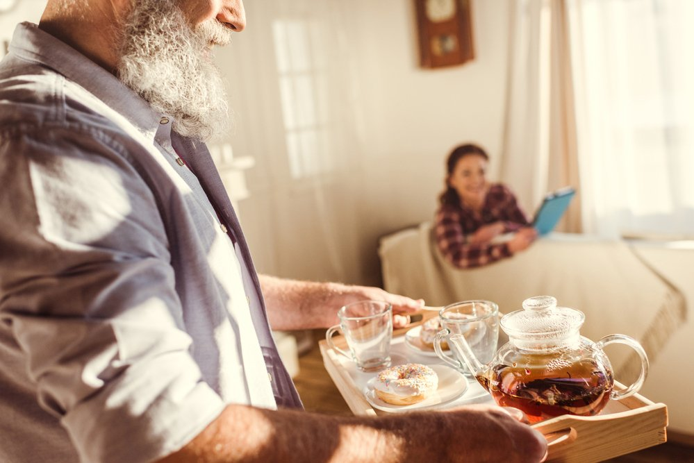 Husband bringing tea to resting wife