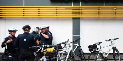 At Queen and Spadina, police detain a man who'd yelled something at them as they'd gone by on bikes. (Michael Chrisman/Torontoist)