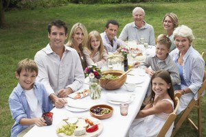 photo of three-generation family having an outdoor picnic on july 4th