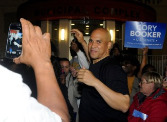 Democratic candidate for US senate Cory Booker gets ready to run with supporters at the Willingboro municipal building Monday evening.