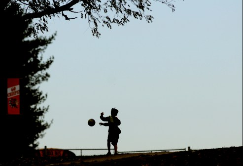 A child plays with a soccer ball on the hill overlooking the Cherokee football field during Monday's group 4 playoff game at Cherokee