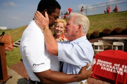 Former Pennsauken coach Vince McAneney, right greets an former player Dwight Hicks before September 13 dedication of the Pennsauken High football field in coach McAneney's name. In the background is his McAneney's wife Holly.